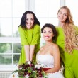 Cheerful bride with bridesmaid holding bouquet — Stock Photo #55861371