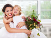 Smiling happy bride and a flower girl indoors — Stock Photo
