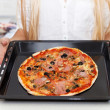 Happy Young Woman Cooking Pizza at Home — Stock Photo #56095233