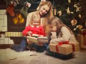 Young mother and her two little daughters with Christmas gifts r — Foto de Stock
