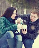 šťastný pár bavit ve winter parku pít horký čaj — Stock fotografie