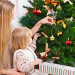 Happy mother and her daughter decorating a Christmas tree — Stock Photo #56414751