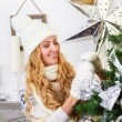 Beautiful young woman decorating Christmas tree — Stock Photo #56414765