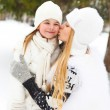 Young blond mother kissing her little daughter outdoors — Stock Photo #56414787