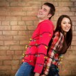 Happy young couple near brick wall with garland — Stockfoto #56414905