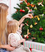 Happy mother and her daughter decorating a Christmas tree — Stock Photo