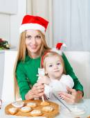 Adorable little girl with her mother baking Christmas cookies — Stock Photo