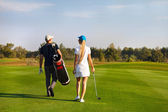 Couple playing golf on a golf course walking to the next hole — Стоковое фото