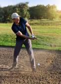 Golfer plays a sand trap shot — Stock Photo