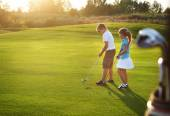 Casual kids at a golf field holding golf clubs — Stock Photo