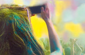 Woman taking photo on mobile phone on holi color festival — Stock Photo