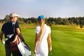 Sportive couple playing golf on a golf course walking to the nex — Stock Photo