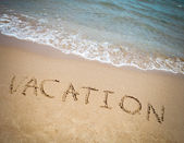 Vacation written in a sandy tropical beach — Stock Photo