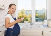 Pregnant woman with healthy food in kitchen — Stock Photo