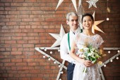 Cheerful married couple standing near the brick wall — Stock Photo