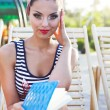 Beautiful pin up girl reading the book near the swimming pool — Stock Photo #64604225