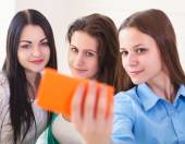 Three smiling teenage girls taking selfie with smartphone camera — Stock Photo