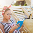 Beautiful pin up girl reading the book near the swimming pool — Stock Photo #64980203