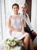 Cheerful married couple near the window — Stock Photo