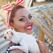 Beautiful pin up girl with puppy near the swimming pool — Stock Photo #65835127