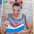 Beautiful pin up girl reading the book near the swimming pool — Stock Photo #65835141