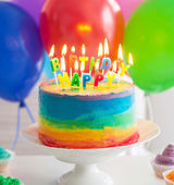 Rainbow cake and cupcakes decorated with birthday candles — Stockfoto