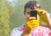 Man taking photo on mobile phone on holi color festival — Stock Photo