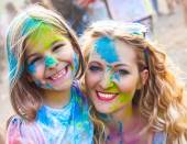 Happy mother with little daughter on holi festival — Stock Photo
