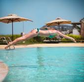 Girl jumping to a swimming pool — Stockfoto