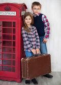 Portrait of a happy girl and a smiling boy with suit case — Stock Photo