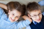 Happy kids are lying together on the floor  — Stock Photo