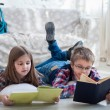 Children readind book in living room — Stock Photo #73112147