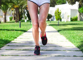 Runner feet running on road in the park. Woman fitness sunrise j — Stock Photo