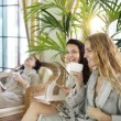 Three young women drinking tea at spa resort — Stock Photo #75735699