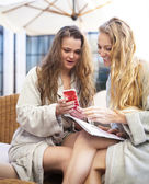 Two young women relaxing in the spa resort wearing toweling robe — Stock Photo