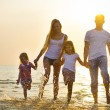 Happy young family having fun running on beach at sunset. Family — Stock Photo #77771094