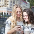 Two happy women friends sharing social media in a smart phone ou — Stock Photo #78883882