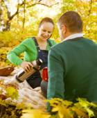 Pregnant couple having picnic in autumn park — Stock Photo