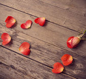 Rose and petal in form heart on wooden background — Stock Photo
