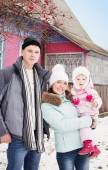 Beautiful family in warm clothes standing  of his house in winte — Stock Photo