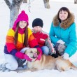 Family with dog in a snowy garden — Stock Photo #53022965