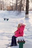 Girl on bench in winter park — Stock Photo