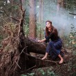 Beautiful witch sitting on a tree trunk in the forest — Stock Photo #53422183