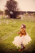 Little girl is playing with bubbles outdoor — Stock Photo