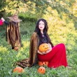 Mother and daughter with pumpkins dressed as witches outdoor — Stock Photo #53460103