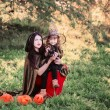 Mother and daughter with pumpkins dressed as witches outdoor — Stock Photo #53462255