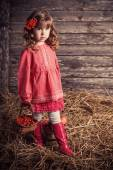 Little girl in pink dress on wooden background — Stock Photo