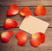Red petal with paper on wooden background — Foto de Stock