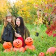 Mother and daughter with pumpkins dressed as witches outdoor — Stock Photo #53901309