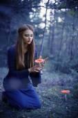 Beautiful witch holding a mushroom — Stock Photo